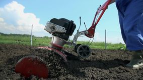Χαμηλό ξυλοφορτώνοντας χώμα καλλιεργητών γωνίας κοντά επάνω σε αργή κίνηση φιλμ μικρού μήκους