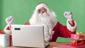 Χαμογελώντας Άγιος Βασίλης κάθεται πίσω από ένα lap-top που ακούει τη μουσική στα ακουστικά και που χορεύει, πράσινο chromakey στ απόθεμα βίντεο