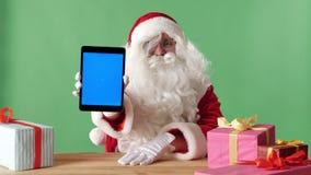 Χαμογελώντας Άγιος Βασίλης που παρουσιάζει ταμπλέτα με την μπλε οθόνη κεκλεισμένων των θυρών, δώρα στον πίνακα, chromakey στο υπό απόθεμα βίντεο
