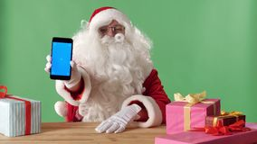 Χαμογελώντας Άγιος Βασίλης που παρουσιάζει smartphone κεκλεισμένων των θυρών, δώρα στον πίνακα, chromakey στο υπόβαθρο απόθεμα βίντεο