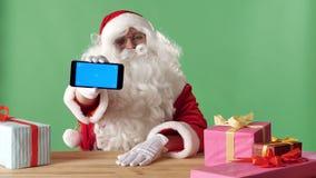 Χαμογελώντας Άγιος Βασίλης που παρουσιάζει smartphone κεκλεισμένων των θυρών, δώρα στον πίνακα, chromakey στο υπόβαθρο φιλμ μικρού μήκους