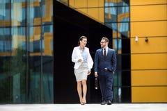 Χαμογελώντας άνδρας και γυναίκα που βγαίνουν το κτίριο γραφείων στοκ εικόνα με δικαίωμα ελεύθερης χρήσης