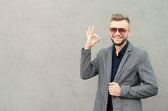 Χαμογελώντας άτομο με μια γενειάδα στα γυαλιά ηλίου και σακάκι που παρουσιάζει εντάξει PL Στοκ Εικόνες
