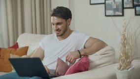 Χαμογελώντας άτομο που εξετάζει τον καναπέ φορητών προσωπικών υπολογιστών στο σπίτι Σκεπτικός τύπος που λειτουργεί on-line φιλμ μικρού μήκους