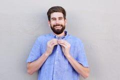 Χαμογελώντας άτομο που κουμπώνει το τοπ κουμπί του πουκάμισου Στοκ Φωτογραφίες