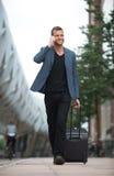 Χαμογελώντας άτομο που περπατά στην πόλη με το κύτταρο και τη βαλίτσα Στοκ φωτογραφίες με δικαίωμα ελεύθερης χρήσης