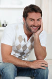 Χαμογελώντας άτομο που χαλαρώνει στο σπίτι Στοκ Φωτογραφία