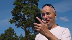 Χαμογελώντας άτομο που χρησιμοποιεί το κινητό τηλέφωνο για την κλήση από την τηλεοπτική συνομιλία στο θερινό πάρκο φιλμ μικρού μήκους