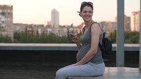 Χαμογελώντας έγκυος γυναίκα με το smartphon απόθεμα βίντεο
