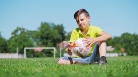 Χαμογελώντας αγόρι με μια σφαίρα ποδοσφαίρου στο αγωνιστικό χώρο ποδοσφαίρου φιλμ μικρού μήκους