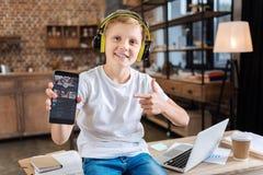 Χαμογελώντας αγόρι που παρουσιάζει αγαπημένη μουσική του που ρέει app Στοκ Φωτογραφίες