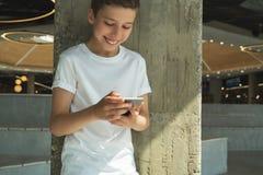 Χαμογελώντας αγόρι στην άσπρη μπλούζα και στάσεις εσωτερικές και smartphone χρήσεων Το αγόρι παίζει τα παιχνίδια στον υπολογιστή  Στοκ Εικόνες