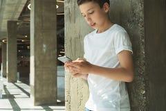Χαμογελώντας αγόρι στην άσπρη μπλούζα και στάσεις εσωτερικές και smartphone χρήσεων Το αγόρι παίζει τα παιχνίδια στον υπολογιστή  Στοκ φωτογραφίες με δικαίωμα ελεύθερης χρήσης
