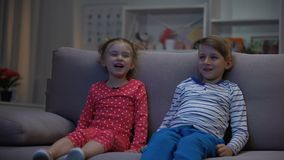 Χαμογελώντας αδελφός και αδελφή που προσέχουν τα αστεία κινούμενα σχέδια μαζί την ψυχαγωγία απόθεμα βίντεο