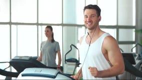 Χαμογελώντας αθλητικό άτομο που τρέχει treadmill απόθεμα βίντεο