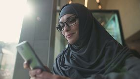 Χαμογελώντας αραβική κυρία στον καφέ που κουβεντιάζει στο τηλέφωνο, εφαρμογή για on-line να ψωνίσει απόθεμα βίντεο