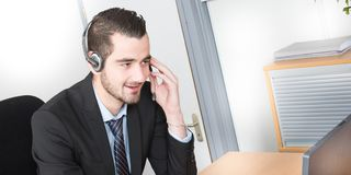 χαμογελώντας αρσενικός κεντρικός χειριστής κλήσης που κάνει την εργασία του με μια κάσκα στοκ εικόνες με δικαίωμα ελεύθερης χρήσης