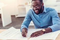 Χαμογελώντας αρσενικός μηχανικός που εργάζεται στο τεχνικό σχέδιο στον πίνακα Στοκ Εικόνες