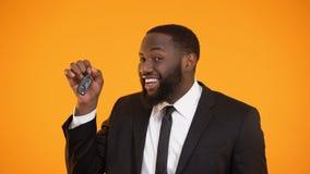 Χαμογελώντας αρσενικό αφροαμερικάνων που παρουσιάζει αυτοκινητικά κλειδιά, νοικιάζοντας το αυτοκίνητο, μίσθωση απόθεμα βίντεο