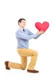 Χαμογελώντας αρσενικό που γονατίζει με το κόκκινο αντικείμενο μορφής καρδιών Στοκ εικόνα με δικαίωμα ελεύθερης χρήσης