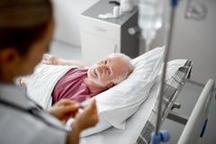 Χαμογελώντας ασθενής που εξετάζει το γιατρό ενώ αυτή που ελέγχει την ενδοφλέβια σταλαγματιά στοκ εικόνες με δικαίωμα ελεύθερης χρήσης