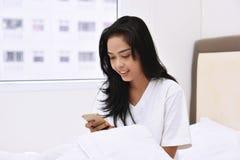 Χαμογελώντας ασιατική γυναίκα που χρησιμοποιεί την κινητή τηλεφωνική συνεδρίαση στο κρεβάτι Στοκ Εικόνες