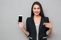 Χαμογελώντας ασιατική επιχειρησιακή γυναίκα που παρουσιάζει κενή οθόνη smartphone Στοκ φωτογραφία με δικαίωμα ελεύθερης χρήσης