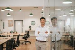 Χαμογελώντας ασιατικός επιχειρηματίας που κλίνει ενάντια σε έναν τοίχο γυαλιού στην εργασία Στοκ εικόνες με δικαίωμα ελεύθερης χρήσης