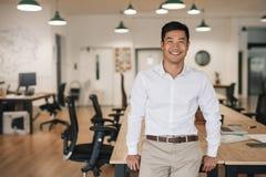 Χαμογελώντας ασιατικός επιχειρηματίας που κλίνει σε έναν πίνακα σε ένα γραφείο Στοκ Εικόνα