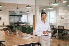 Χαμογελώντας ασιατικός επιχειρηματίας που χρησιμοποιεί μια ταμπλέτα σε ένα γραφείο Στοκ Εικόνες