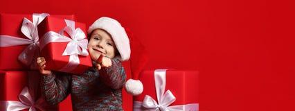 Χαμογελώντας αστείο παιδί στο κόκκινο δώρο Χριστουγέννων εκμετάλλευσης καπέλων Santa υπό εξέταση Έννοια Χριστουγέννων στοκ εικόνες με δικαίωμα ελεύθερης χρήσης
