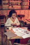 Χαμογελώντας αφρικανική κυρία που κάνει τη συνεδρίαση σχεδίων σχεδίου μόδας στην καφετέρια στοκ φωτογραφία