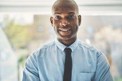 Χαμογελώντας αφρικανικός επιχειρηματίας που στέκεται μόνο σε ένα γραφείο Στοκ φωτογραφίες με δικαίωμα ελεύθερης χρήσης