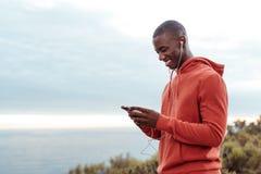 Χαμογελώντας αφρικανικό άτομο που ακούει τη μουσική έξω jogging Στοκ φωτογραφία με δικαίωμα ελεύθερης χρήσης