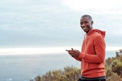 Χαμογελώντας αφρικανικό άτομο που ακούει τη μουσική πριν από ένα τρέξιμο Στοκ Φωτογραφίες