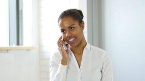 Χαμογελώντας αφροαμερικανίδα γυναίκα που μιλά με τον πελάτη σε Smartphone Στοκ φωτογραφία με δικαίωμα ελεύθερης χρήσης