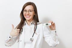 Χαμογελώντας βέβαια νέα γυναίκα γιατρών στην ιατρική εσθήτα με τα γυαλιά στηθοσκοπίων που παρουσιάζουν αντίχειρες, κλινικός ηλεκτ στοκ φωτογραφία