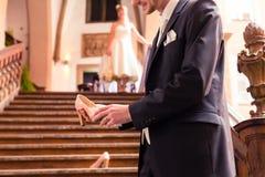 Χαμογελώντας γαμπρός που κρατά το υψηλό τακούνι στο χέρι του στοκ φωτογραφία