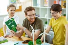 Χαμογελώντας γενειοφόρος δάσκαλος που είναι ευχαριστημένος από το συμφέρον των νέων μαθητών του στοκ φωτογραφία