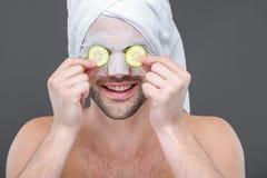χαμογελώντας γενειοφόρο άτομο με τις φέτες μασκών και αγγουριών κολλαγόνων στα μάτια, Στοκ Εικόνα
