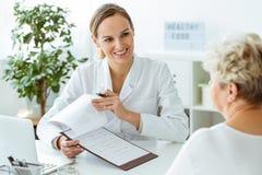 Χαμογελώντας γιατρός κατά τη διάρκεια των ιατρικών εξετάσεων στοκ εικόνα