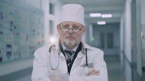 Χαμογελώντας γιατρός που διασχίζει τα χέρια και που εξετάζει τη κάμερα 4K απόθεμα βίντεο