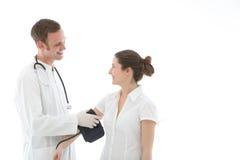 Χαμογελώντας γιατρός που παίρνει μια ανάγνωση πίεσης του αίματος Στοκ εικόνα με δικαίωμα ελεύθερης χρήσης