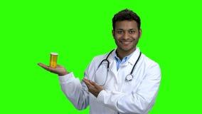 Χαμογελώντας γιατρός που παρουσιάζει τα χάπια στην πράσινη οθόνη απόθεμα βίντεο