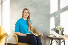 Χαμογελώντας γραφείο συνεδρίασης γυναικών στο σπίτι και εξέταση τη κάμερα Στοκ Εικόνες