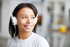 Χαμογελώντας γυναίκα αναμιγνύω-φυλών που ακούει τη μουσική στοκ φωτογραφία με δικαίωμα ελεύθερης χρήσης