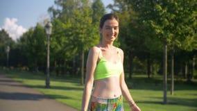 Χαμογελώντας γυναίκα ικανότητας που παίρνει έναν περίπατο μετά από το workout φιλμ μικρού μήκους