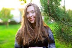 Χαμογελώντας γυναίκα κοντά στο ξύλο κέδρων με το πράσινο υπόβαθρο χλόης Στοκ Εικόνες