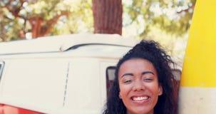 Χαμογελώντας γυναίκα με την ιστιοσανίδα που στέκεται κοντά camper van 4k φιλμ μικρού μήκους