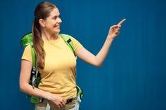 Χαμογελώντας γυναίκα με το σακίδιο πλάτης ταξιδιού που δείχνει το δάχτυλο Στοκ Εικόνες